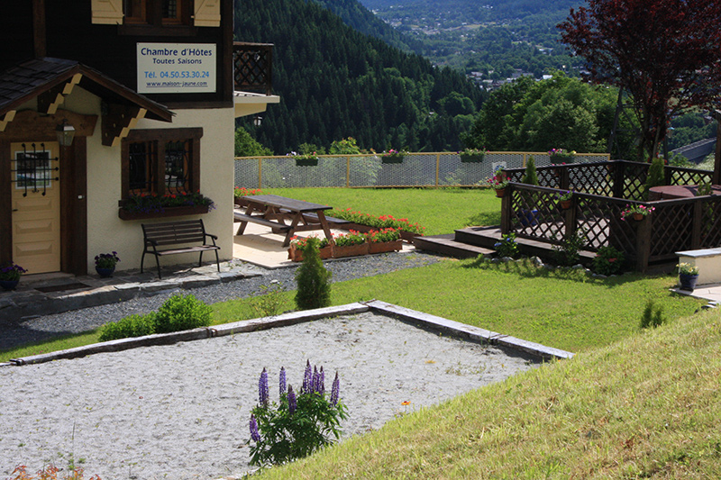 Petanque pitch, hot tub deck and red geraniums around the picnic benches